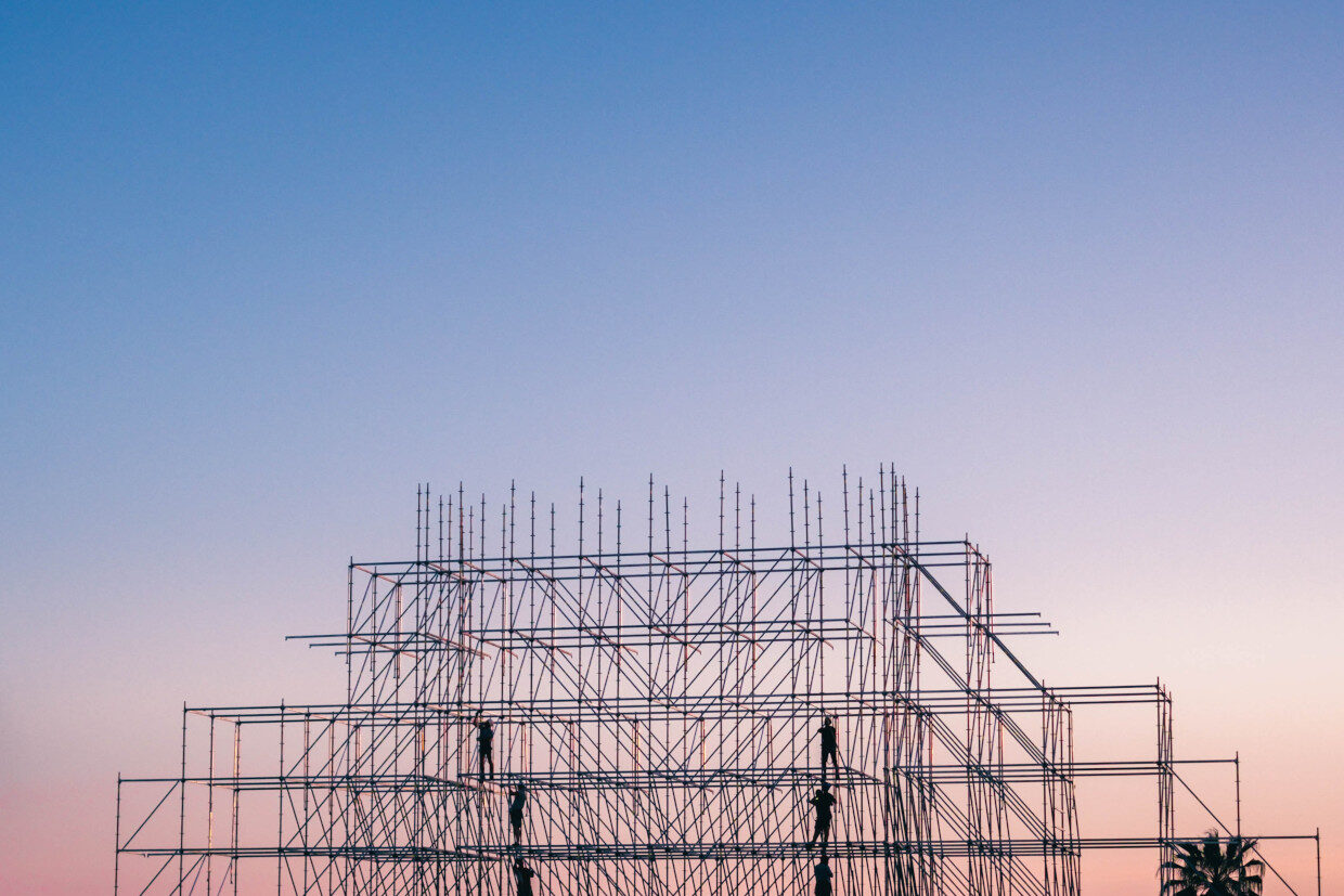 Scaffolders erecting scaffolding against sunset