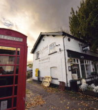 Picture of shop with white front and red phone box